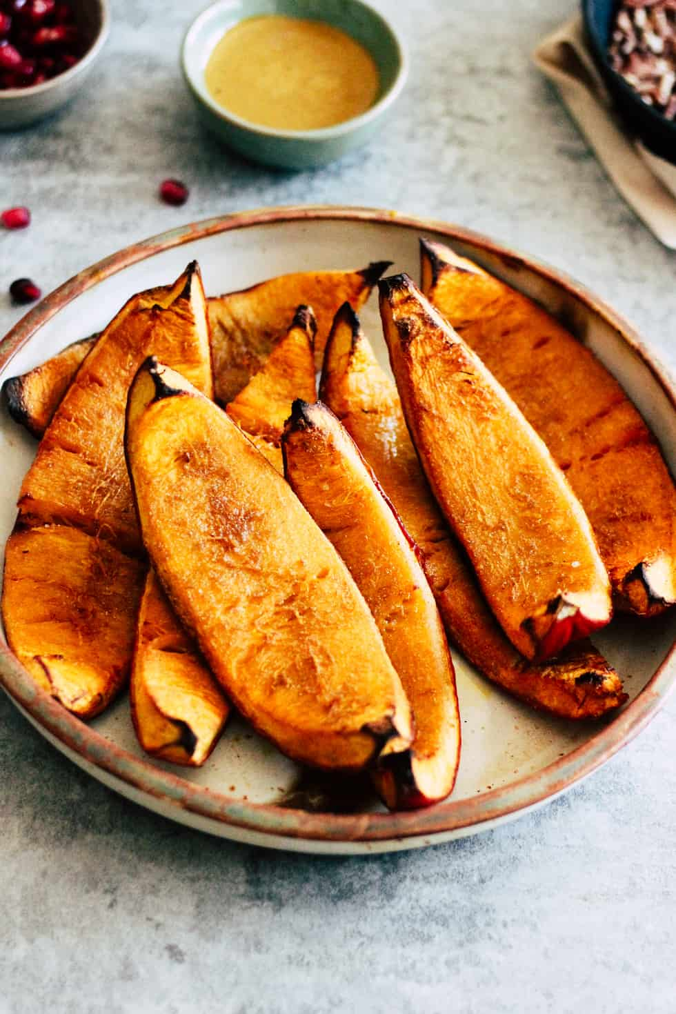 Roasted pumpkin wedges in ceramic dish.
