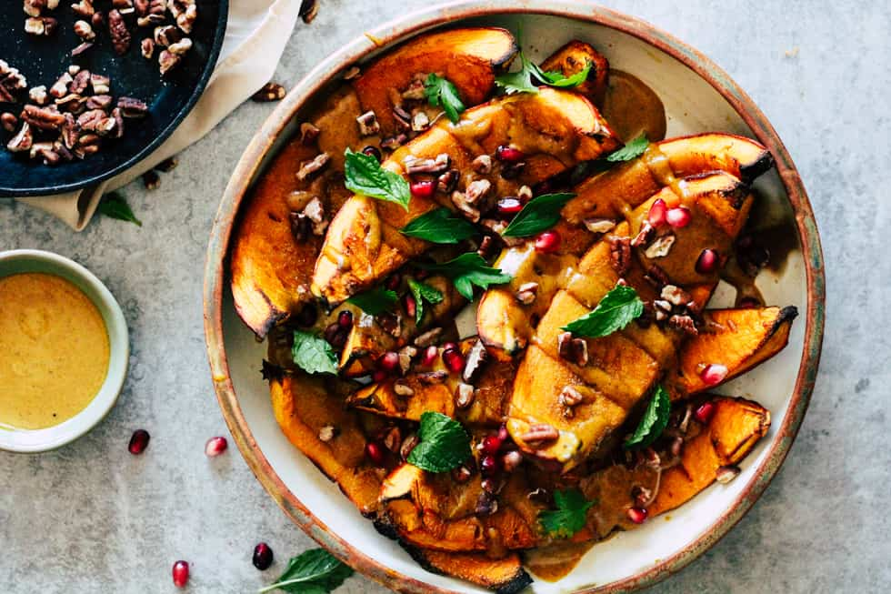Roasted squash in dish with yellow curry sauce.