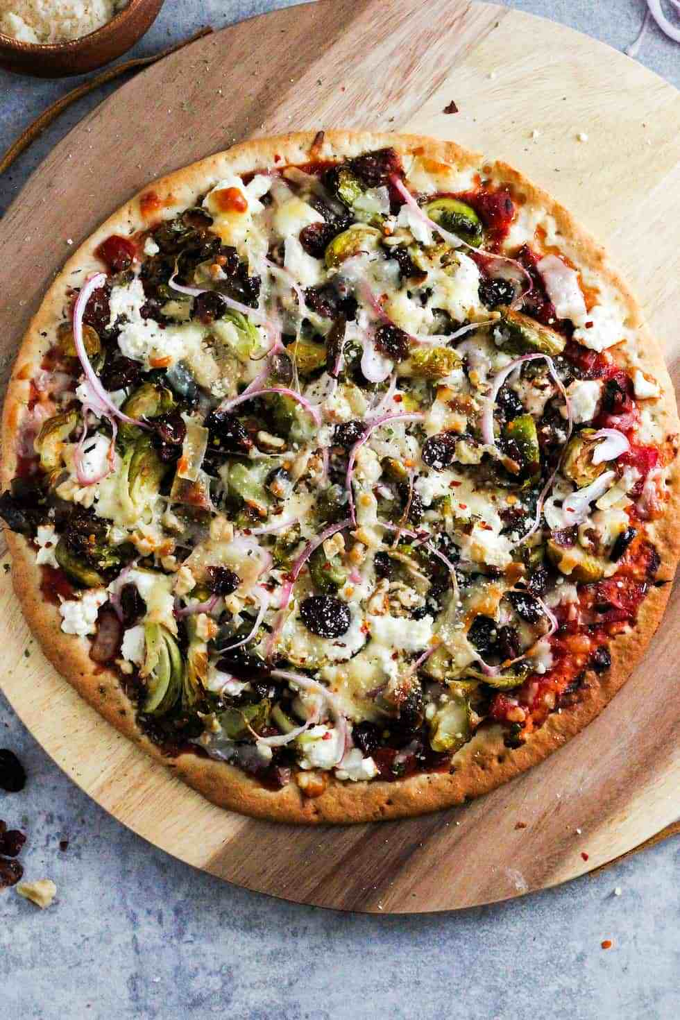 Brussels sprouts pizza on round wooden board.