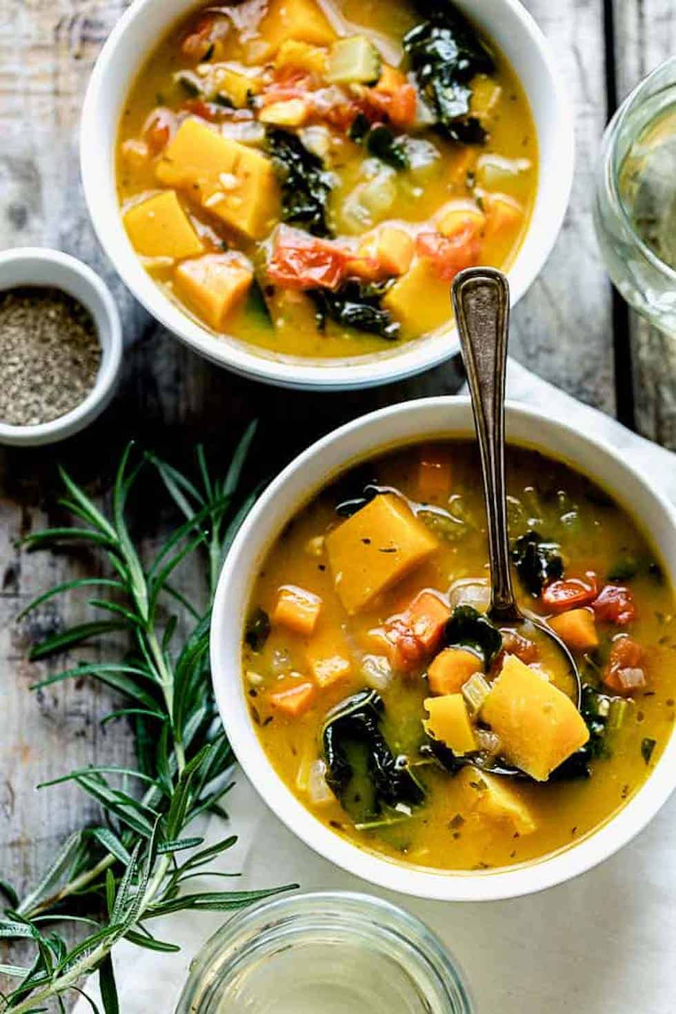 Vegan soup recipes, including vegetable soup in white bowls with rosemary.