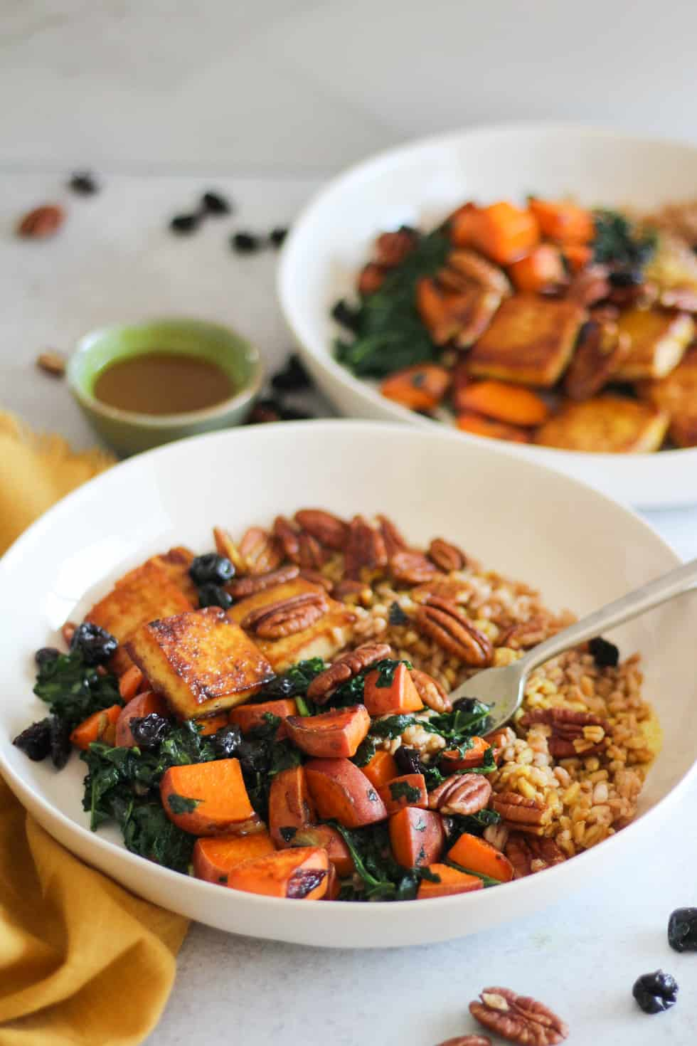 Baked Tofu Harvest Bowls with sweet potato and kale in white bowls with yellow napkin.