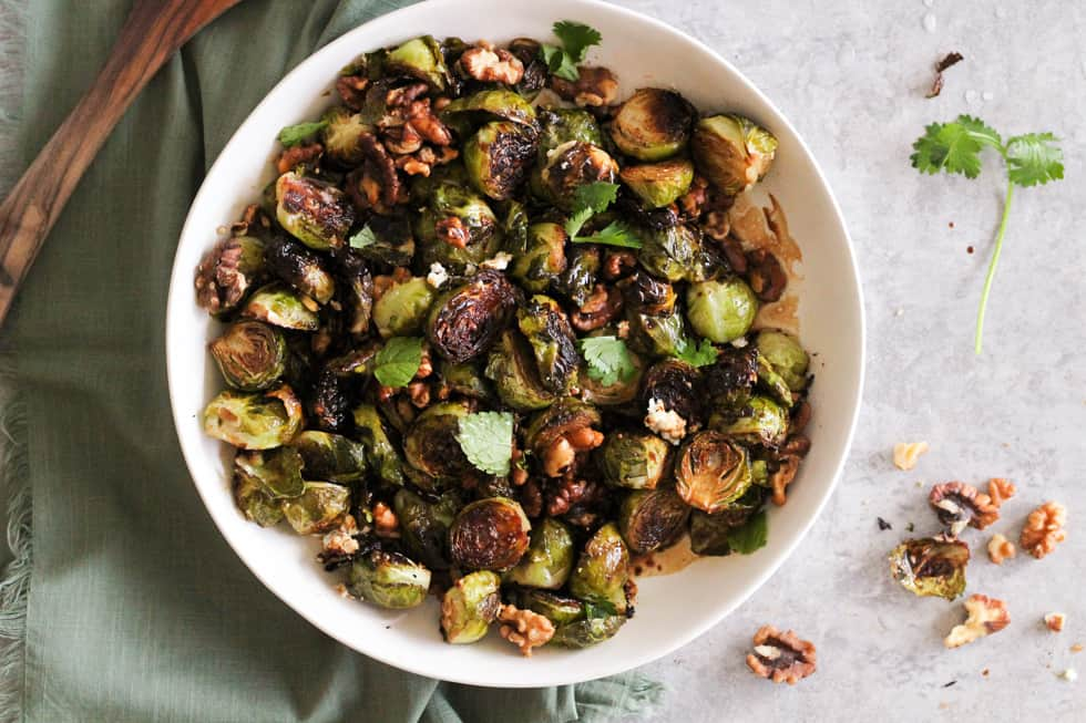 Horizontal image of roasted brussels sprouts in white dish with green napkin.