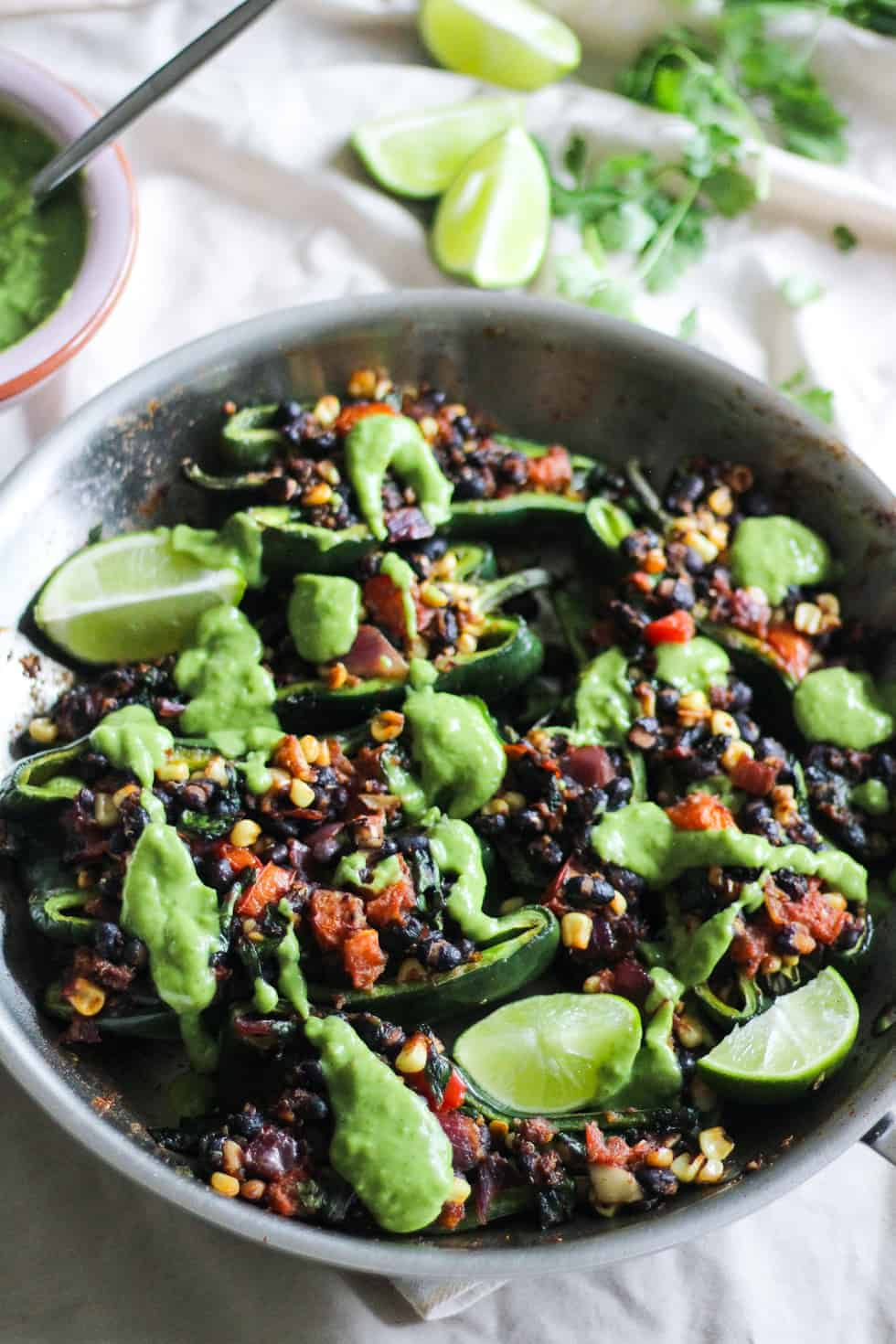 Skillet filled with vegan Stuffed Poblano Peppers with green sauce.