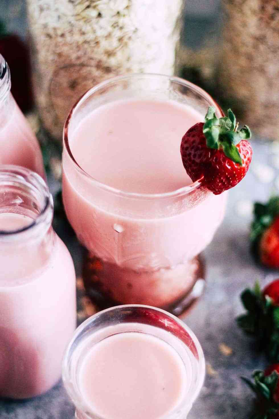 Vegan Strawberry Oat Milk in a pink glass with strawberry milk bottles next to it.