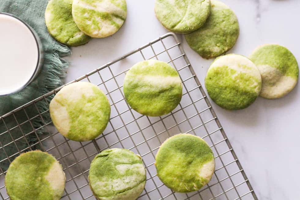 Horizontal image of marbled matcha sugar cookies on wire rack with a glass of milk.