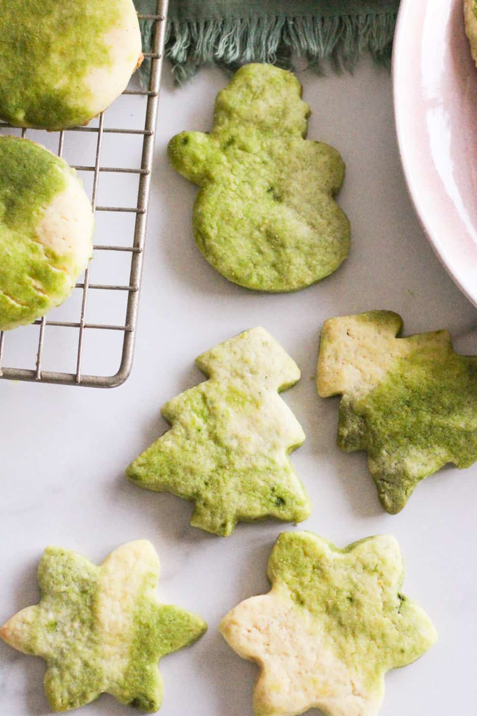 Matcha sugar cookies in Christmas shapes on white marble.