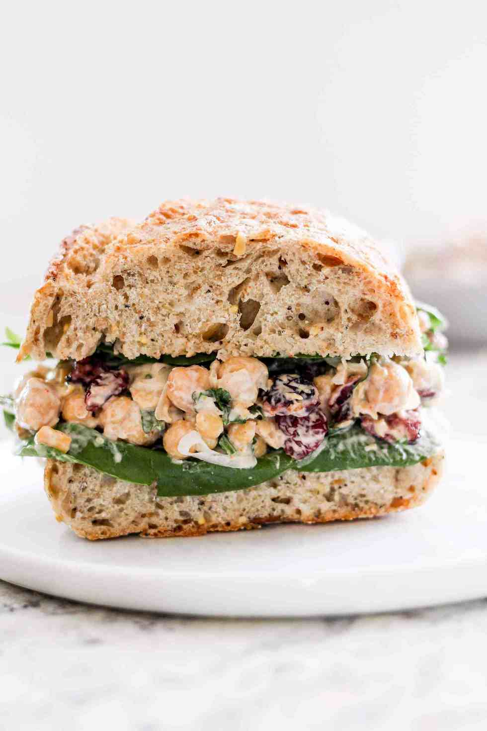 Cranberry Chickpea Salad on a sandwich on a white plate as an example of vegetarian lunches to pack for work or school.