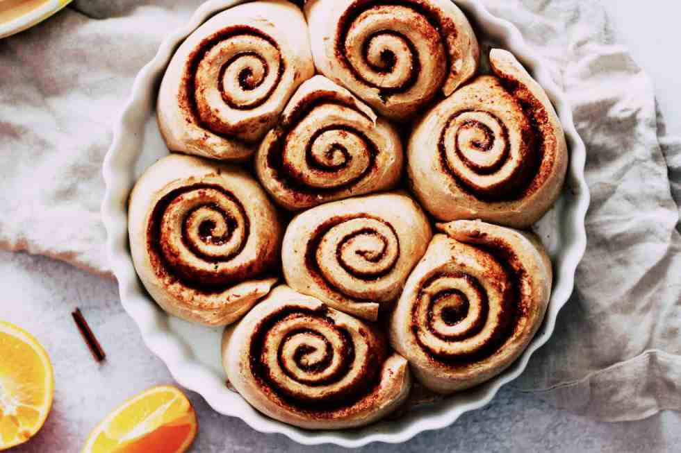 Horizontal image of cinnamon rolls in a white, round baking dish.