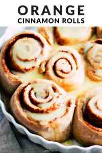 "Sweet rolls with cream cheese glaze in a white baking dish with text that reads, ""Orange Cinnamon Rolls."""