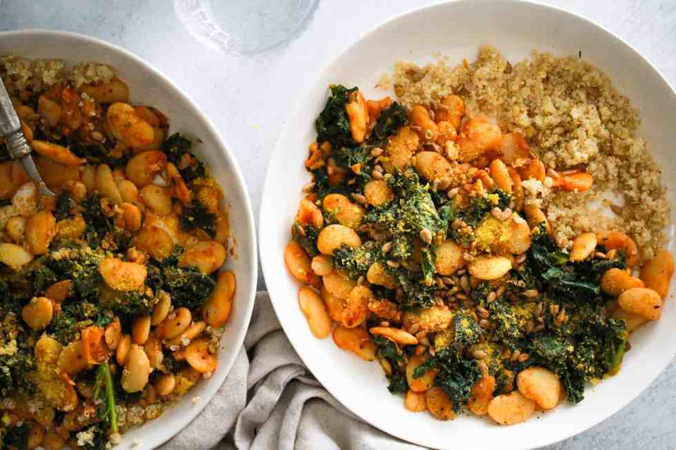 Lima beans and greens in white bowls with quinoa.