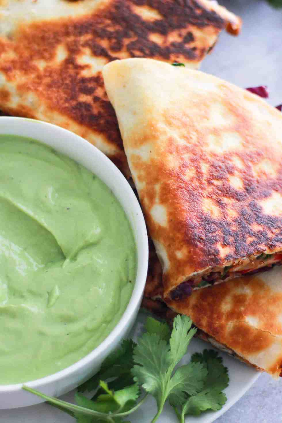 Bean quesadilla on a plate with avocado dipping sauce.