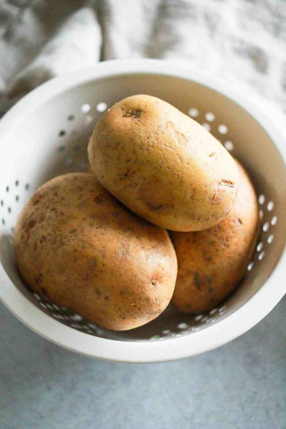 Gold potatoes in a white colander.