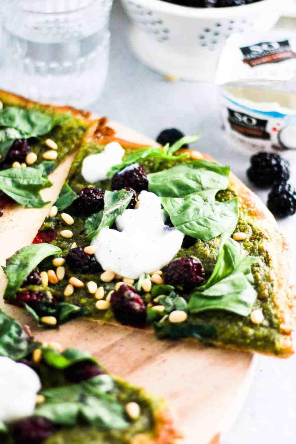 Sliced vegan pesto pizza with carton of So Delicious Coconut milk yogurt in the background.
