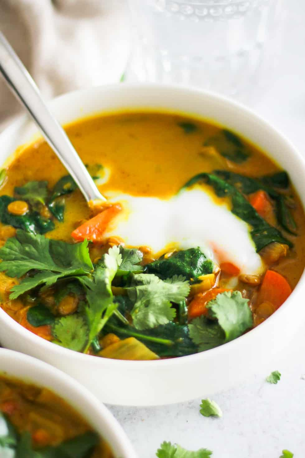 Yellow soup in white bowl with yogurt and cilantro topping.