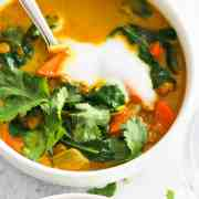Vegan Turmeric Soup in white bowls with cilantro and yogurt.