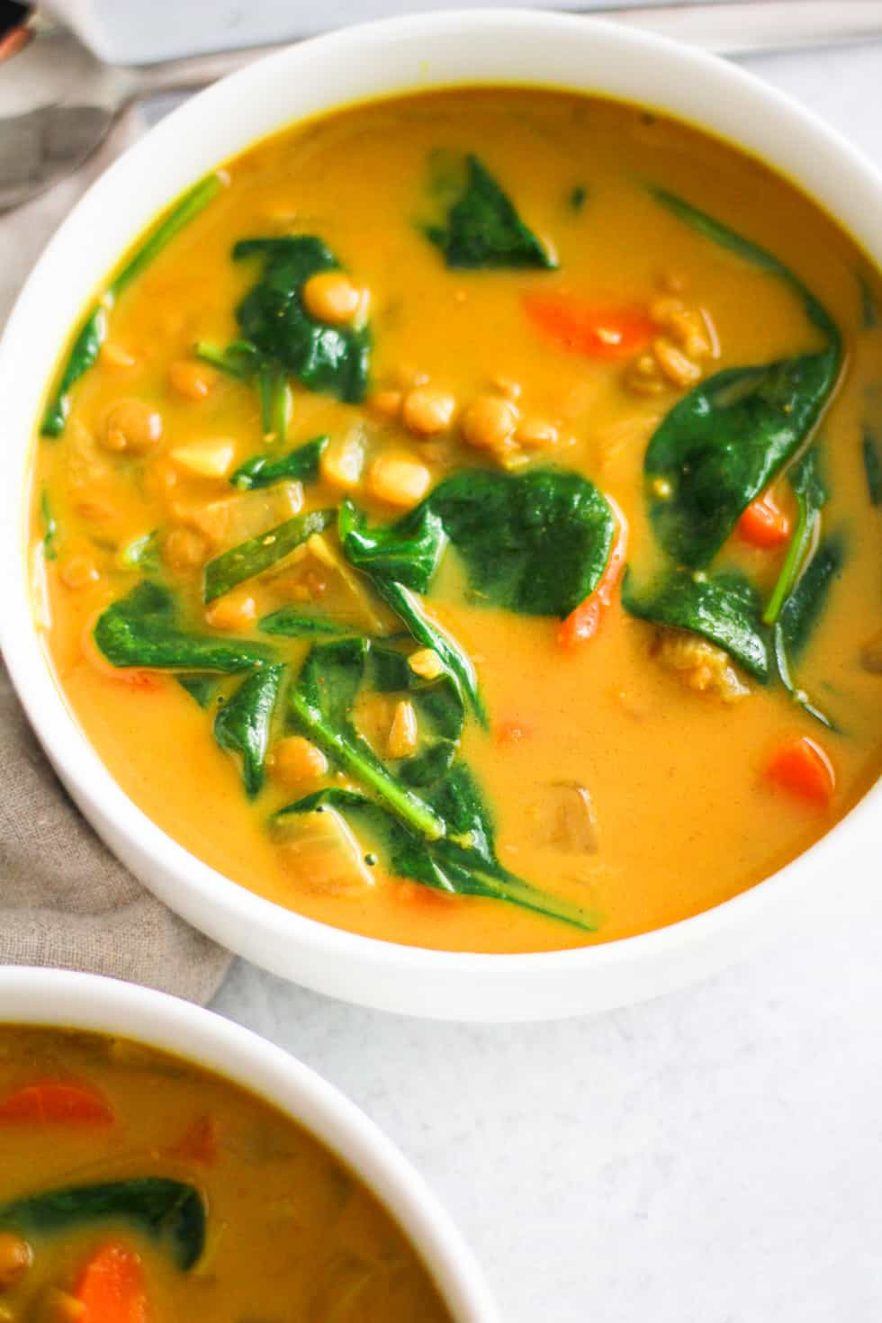 lentils and spinach in a bowl of stew.