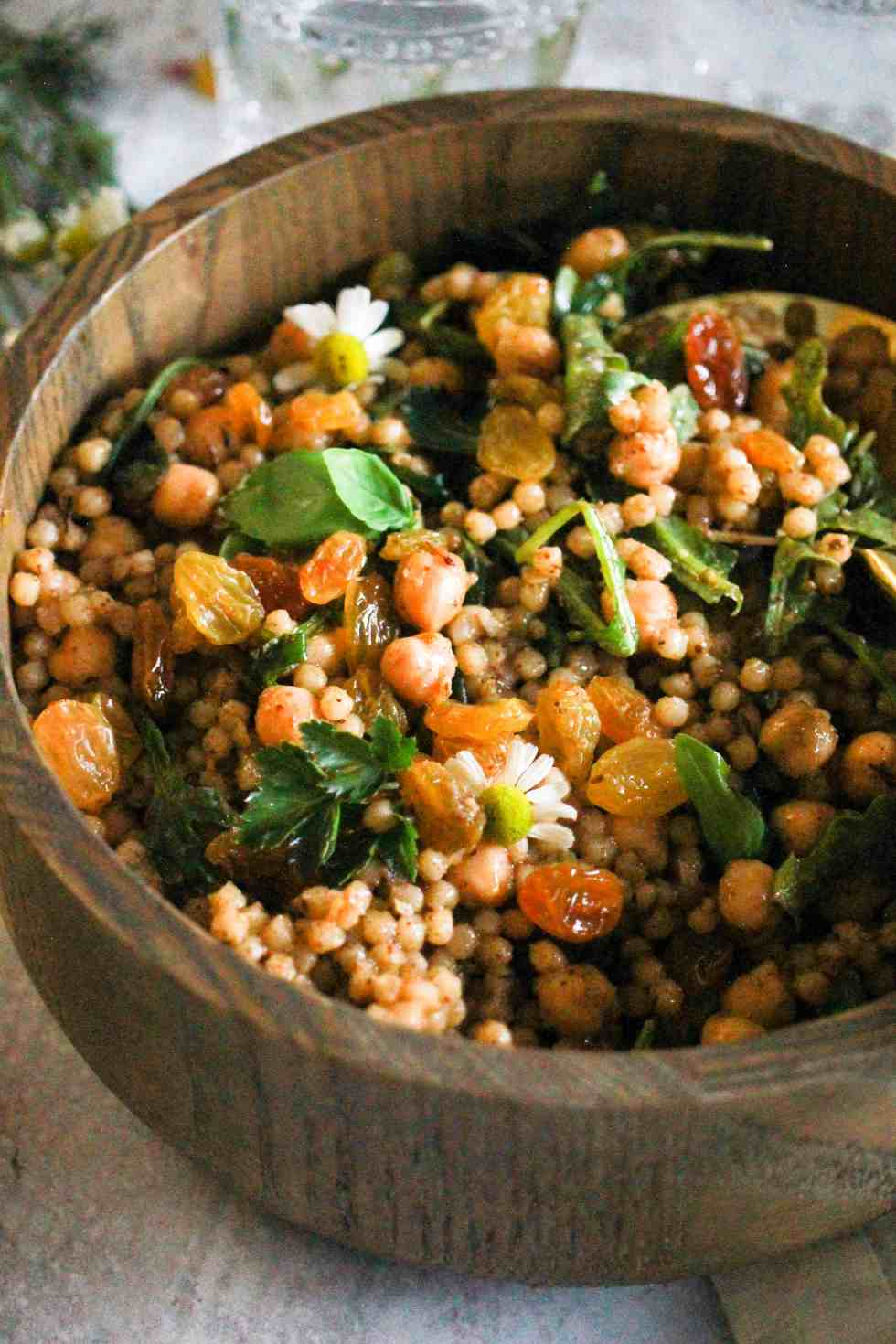 Israeli couscous with chickpeas and golden raisins in a wooden bowl.