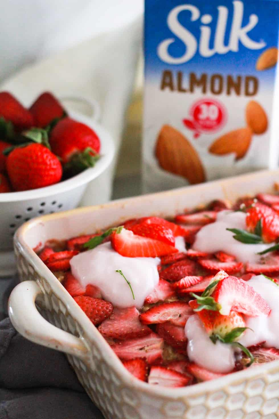 Vegan baked oatmeal in a white dish with fresh strawberries and a carton of Silk almond milk.