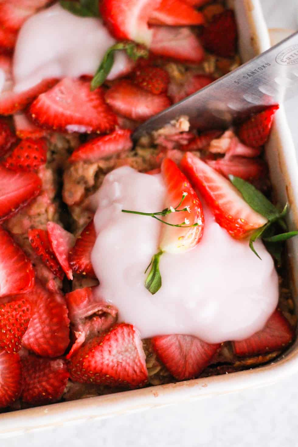 Closeup shot of knife cutting into strawberry baked oatmeal.