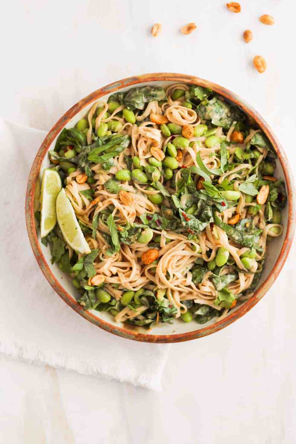 Peanut noodles in a brown ceramic dish with fresh lime for easy college meals