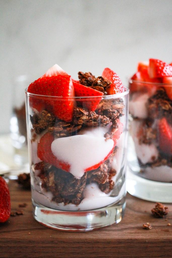 strawberry yogurt parfaits in glasses on wood board