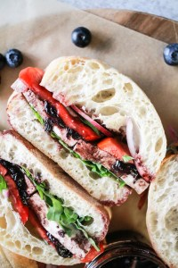 Tomato Mozzarella Sandwich with blueberry sauce and fresh blueberries in the background.