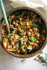 Pearl couscous salad in wooden bowl with turquoise and gold serving spoon