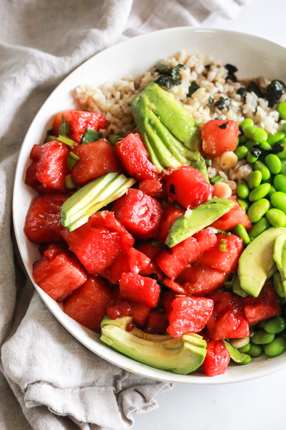watermelon, avocado and edamame bowls with linen napkin