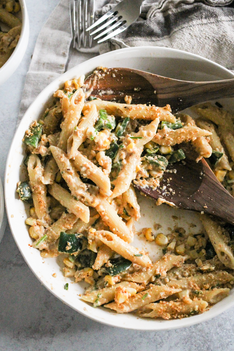 Cheesy pasta in a white bowl with wooden serving spoon.
