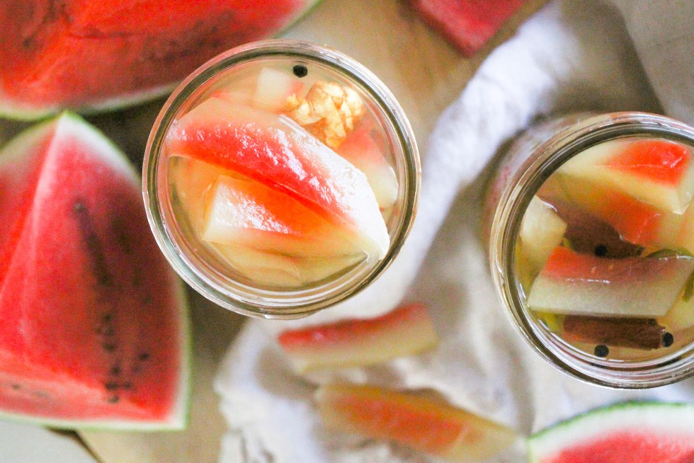 Horizontal overhead image of pickled watermelon rind in glass jars with sliced watermelon around them.