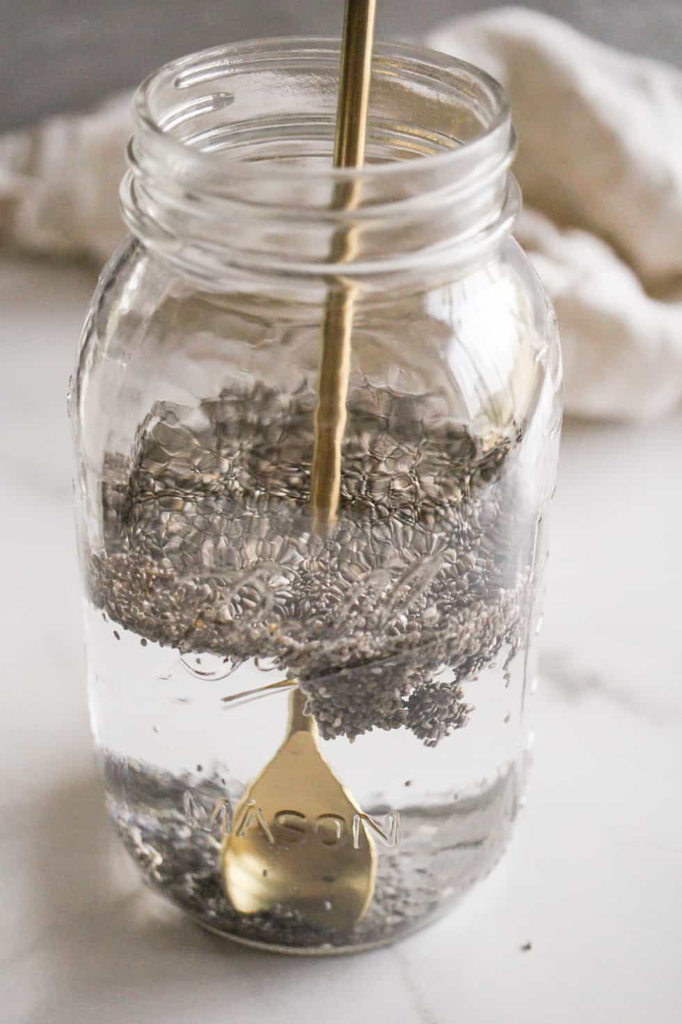 Chia seeds in a jar of water being stirred with a gold spoon.