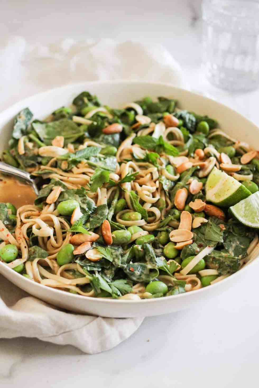 Closeup image of peanut noodles with edamame in a white bowl.