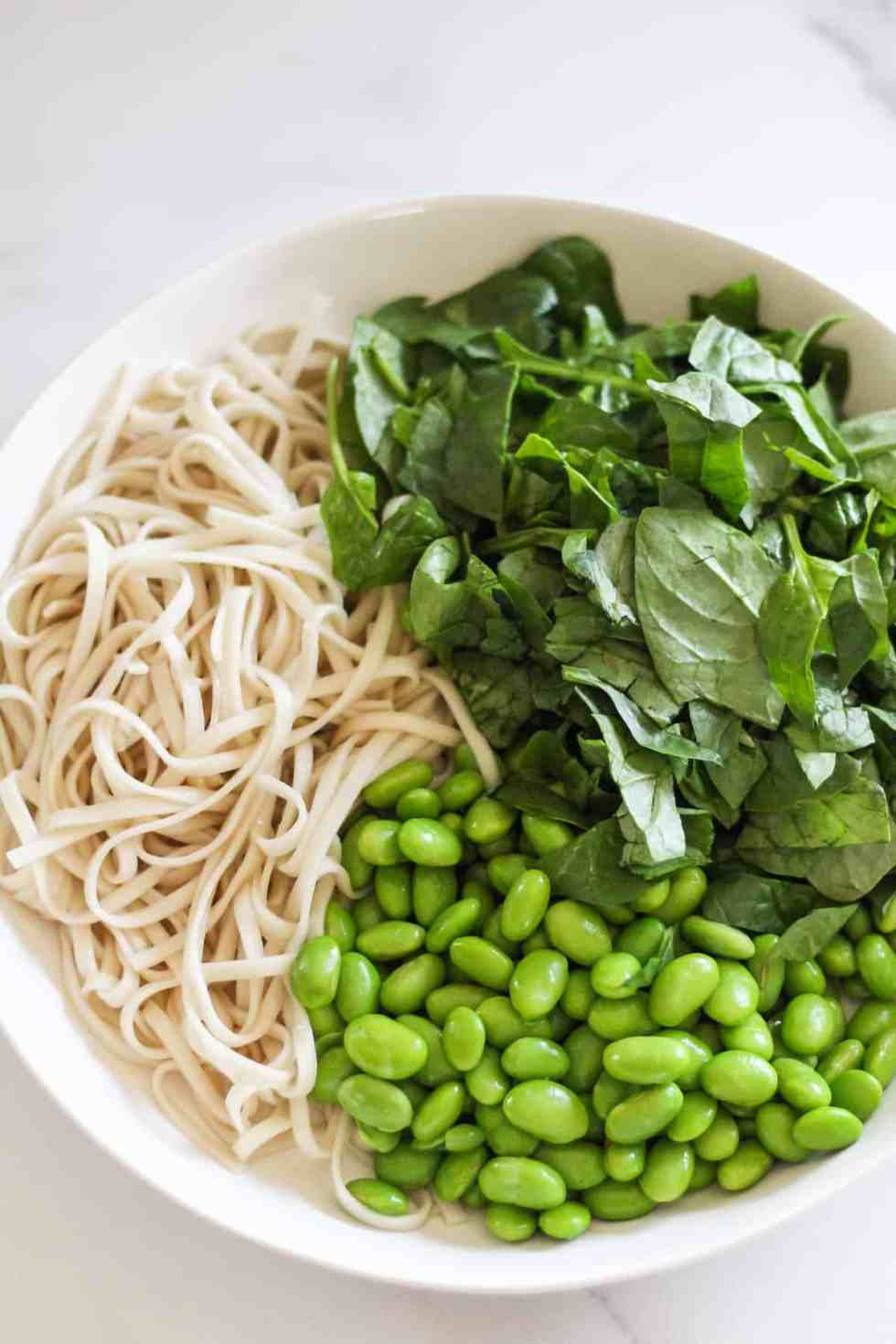 Noodles, edamame, and chopped spinach in a white bowl.