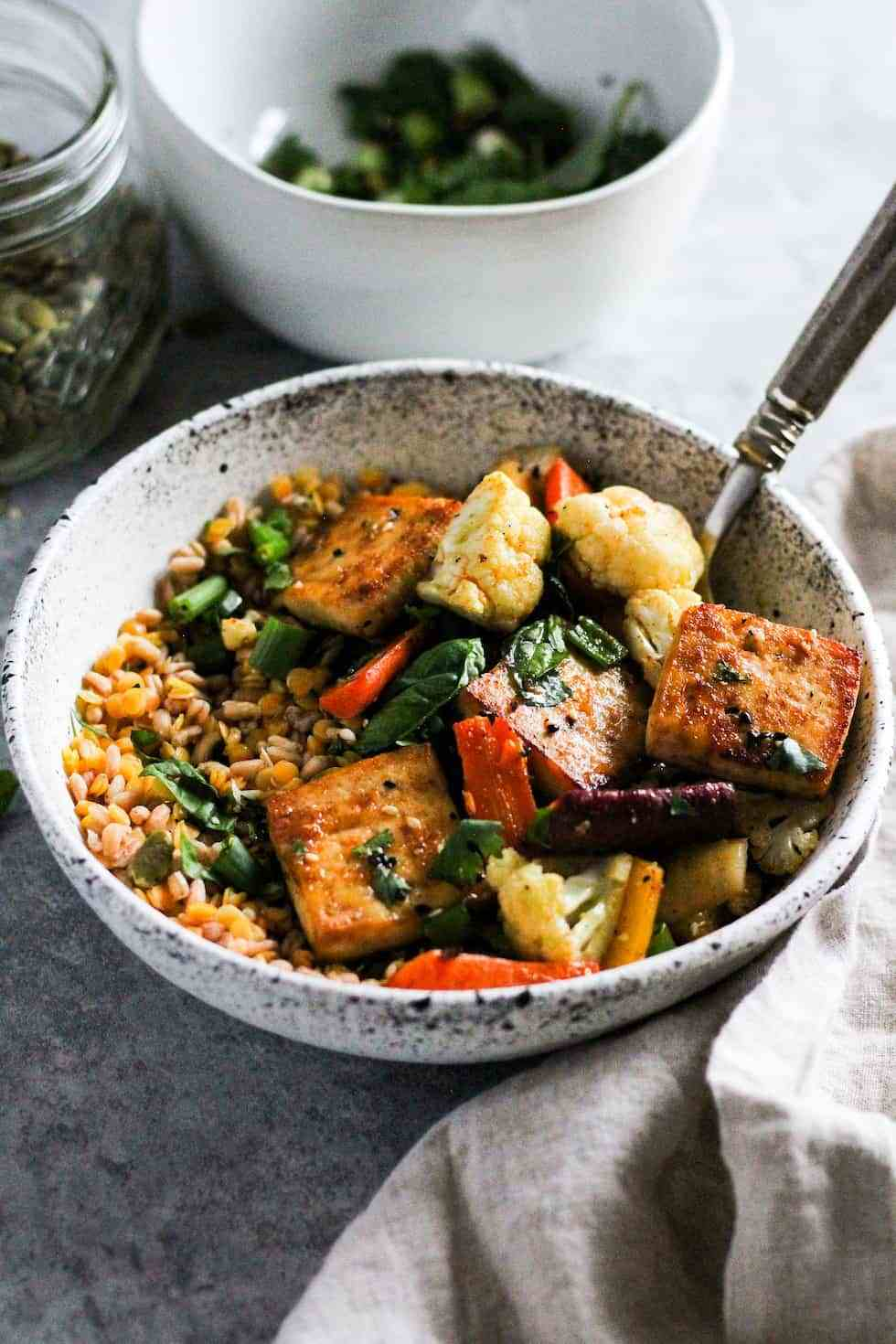 Tofu and veggies in white bowls on grey background.