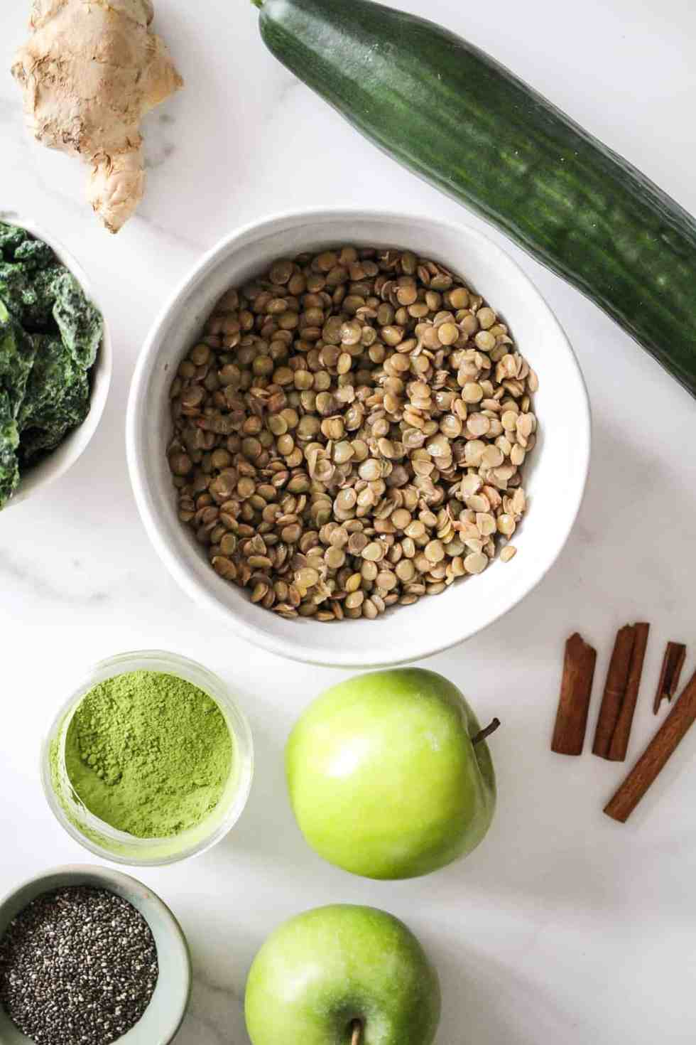 Flatlay image of lentil smoothie ingredients, including cooked lentils, apples, cucumber, cinnamon, ginger, matcha, and chia seeds.