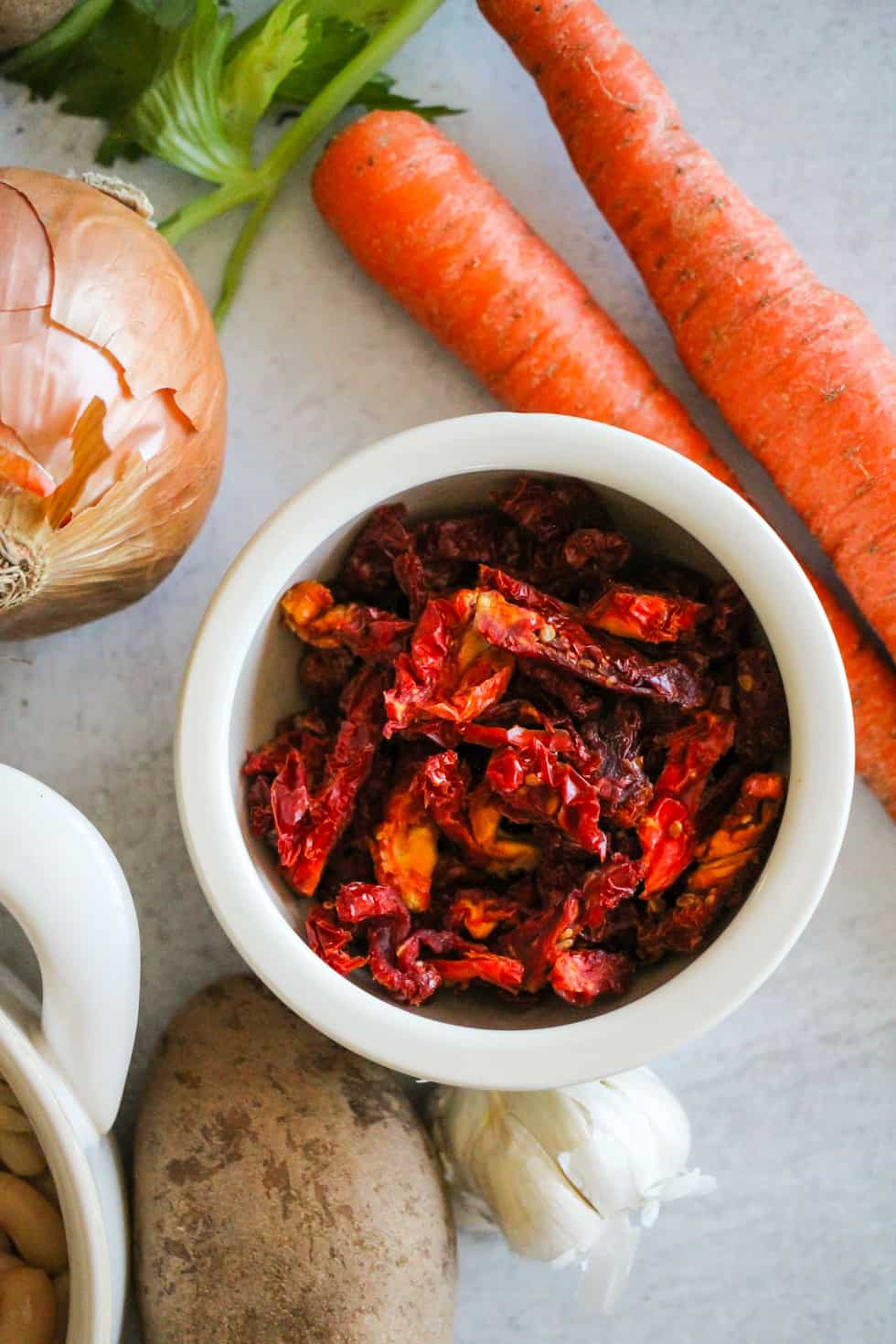 Bowl of sun-dried tomatoes with carrots, onion, and potato