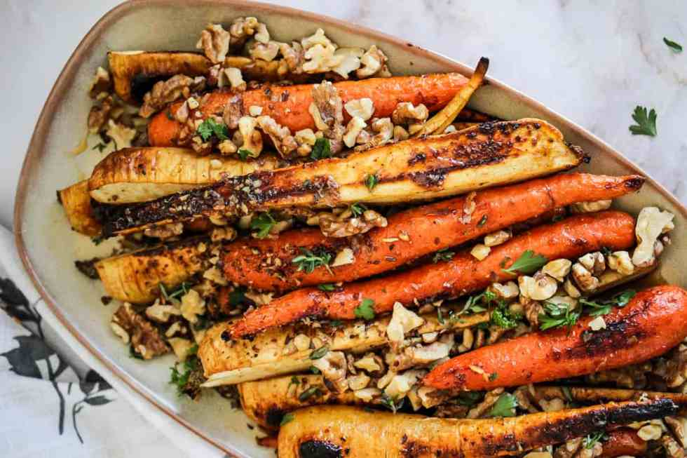 Horizontal overhead image of roasted carrots and parsnips with walnuts and green herbs.