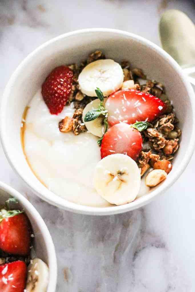 Closeup of a vegan granola bowl with macadamia nut granola, strawberries, and bananas.