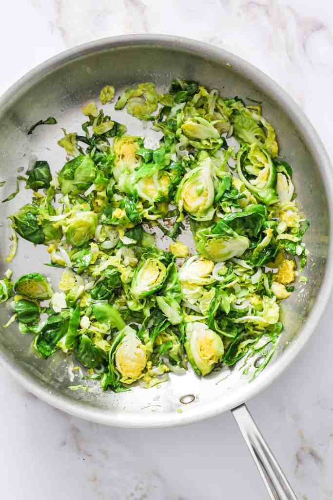 Brussels sprouts sautéing in a skillet.