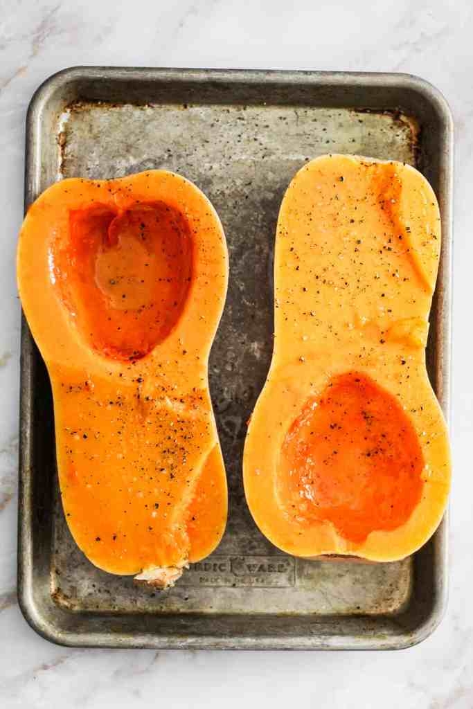 Halved butternut squash on a rimmed baking sheet.