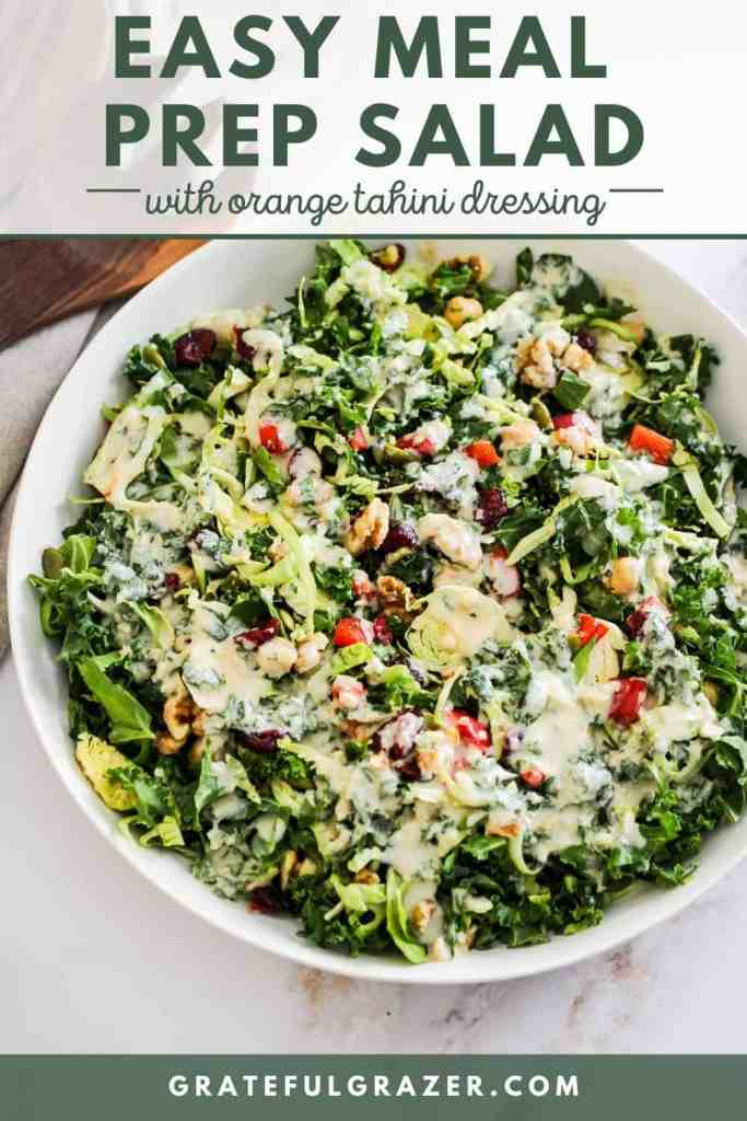 """Bowl of kale salad with brussels sprouts and chickpeas with tahini dressing drizzled on top. Text reads, """"Easy Meal Prep Salad with Orange Tahini Dressing; GratefulGrazer.com."""""""