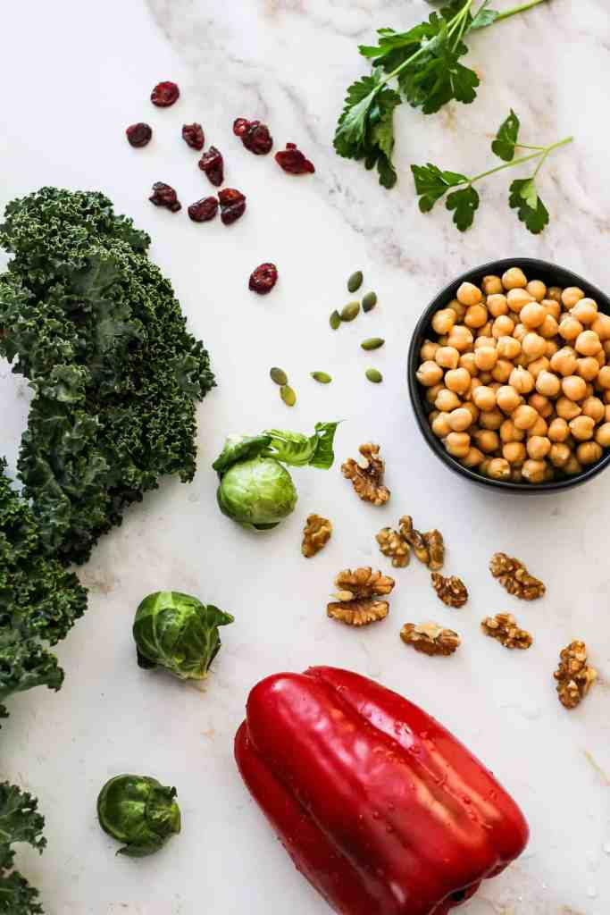 Flat-lay image of kale, parsley, chickpeas, cranberries, pepitas, Brussels sprouts, and walnuts on a white marble background.