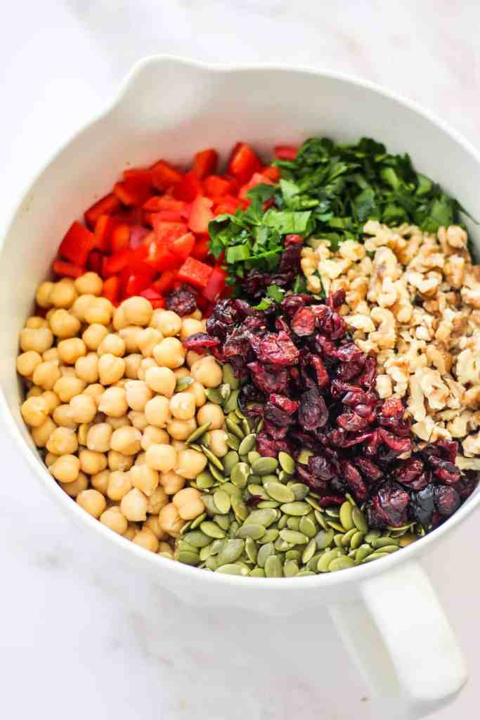 Chickpeas, pepitas, dry cranberries, walnuts, parsley, and diced bell pepper in a large mixing bowl.