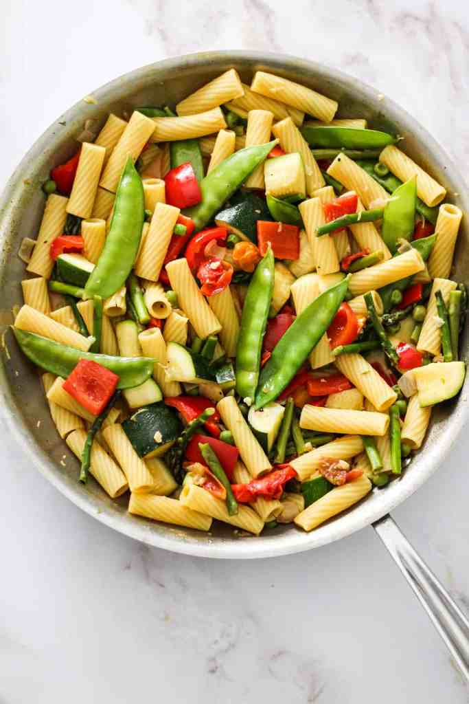 Vegetables and pasta in a skillet on a white marble countertop.