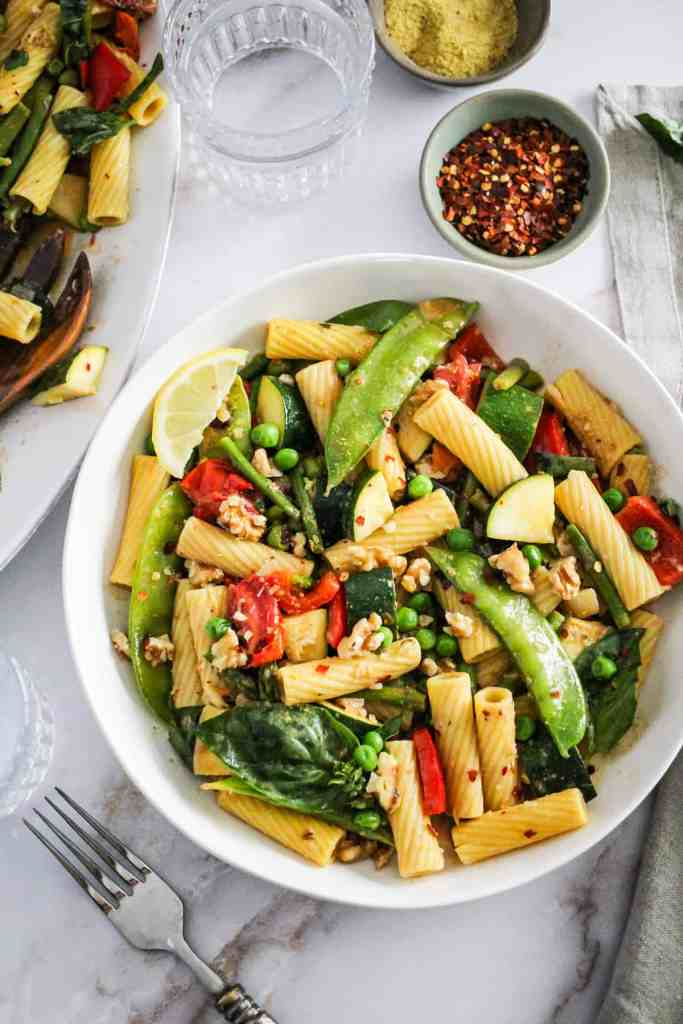 Overhead image of Vegan Pasta Primavera in a white bowl on a marble background.