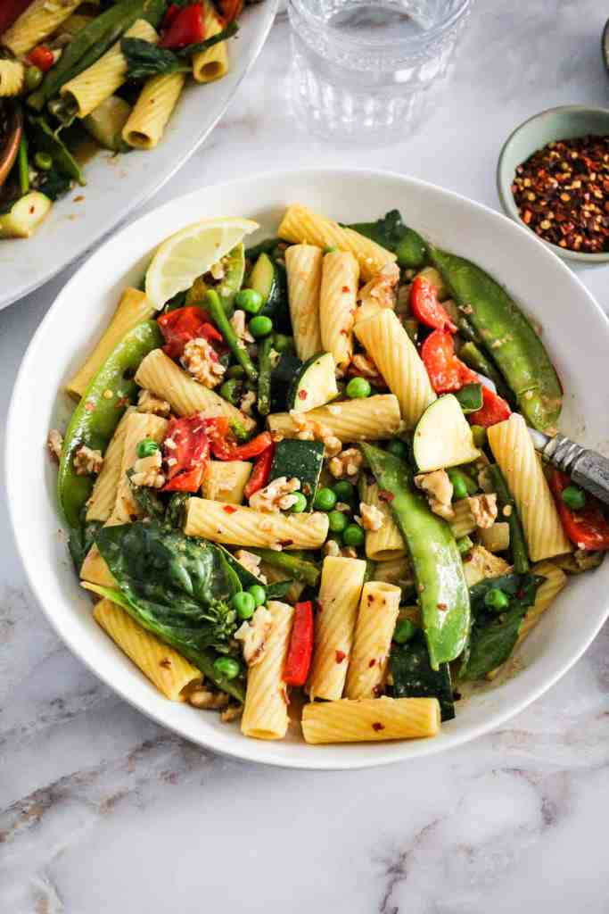 Vegetable rigatoni with walnuts in a white pasta bowl.