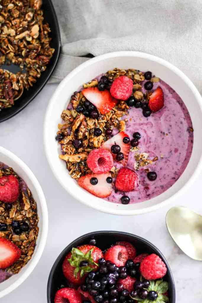 Overhead image of wild blueberry yogurt bowl with fresh berries and granola.
