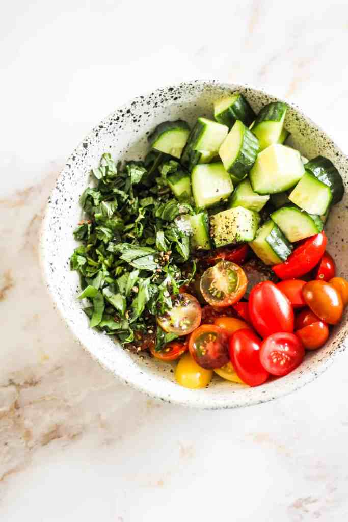 Bowl with cucumber, cherry tomatoes, and fresh herbs with salt and pepper.