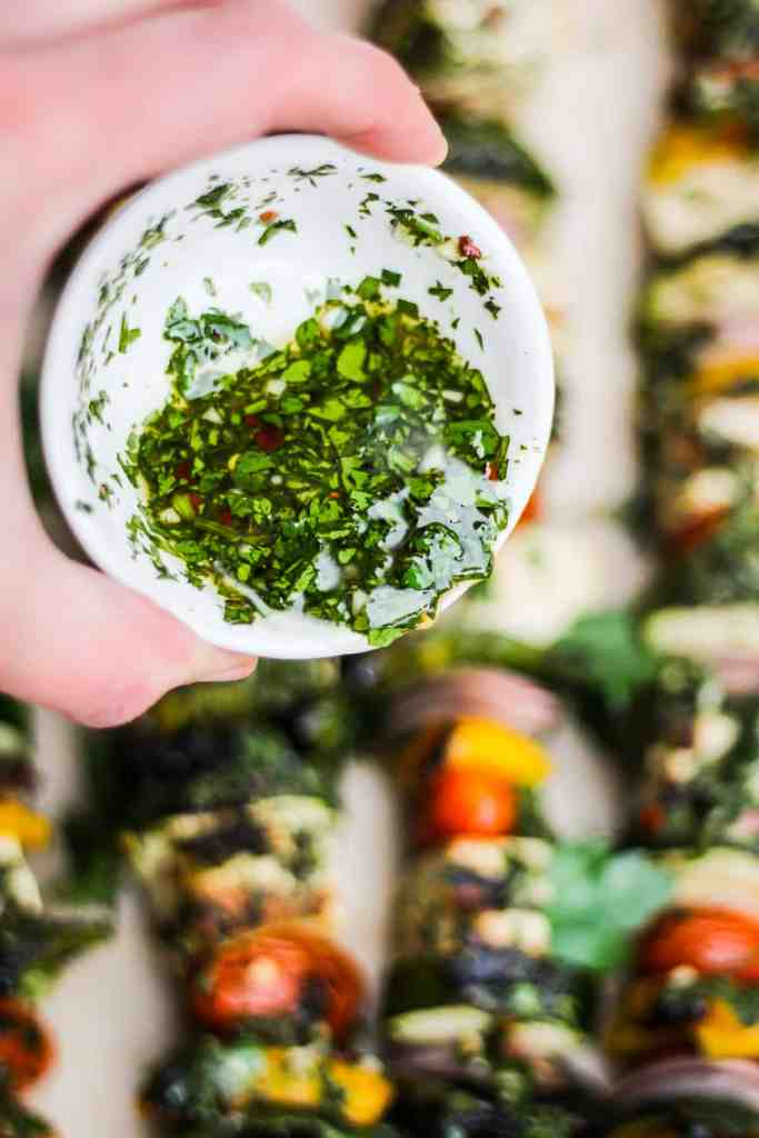 Hand pouring green chimichurri sauce from a small white bowl.