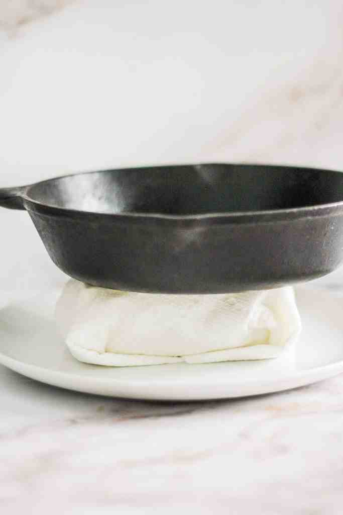 Tofu wrapped in paper towels with a cast iron skillet on top.